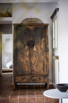 Rustic Chinese cabinet. Interior designer Katrina Phillips transformed a basic 'casita' in the country side of San Juan (Ibiza) into a cozy home. Inside the casita, Katrina's personal style is clearly visible – earthy, natural and authentically bohemian.