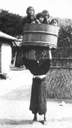 Woman balancing four children on a half barrels on her head. Why???? Old Japan