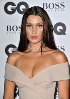 Bella Hadid turned the heat on by putting a very sassy and sex appeal oozing appearance on the red carpet by dressing up in a light coffee shade gown with an off the shoulder and low cut neckline, which drew eye to her ample cleavage and a thigh high side slit, which showed off her long legs, while walking the carpet at the 2016 GQ Men of the Year Awards on September 6, 2016 at Tate Modern in London, England.