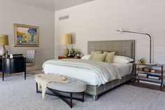 In the master bedroom, a cerused-oak magazine table from Aero—topped with a rare vintage Angelo Lelli articulating lamp—offsets a chest of drawers from R.E. Steele. A vintage Widdicomb desk purchased at JED Antiques in Sag Harbor is paired with an Arthur Lerod chair; the hand-knotted mohair rug by Sacco Carpet lends texture to the polished interior.