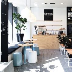 modern coffee shop with whitewashed floors, black accents and pastel touches