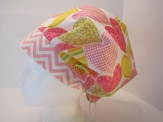 A really cute hat. Hearts in pink and yellow with a pink chevron band. The fabric is 100% cotton of good quality. This hat is a bouffant style hat with