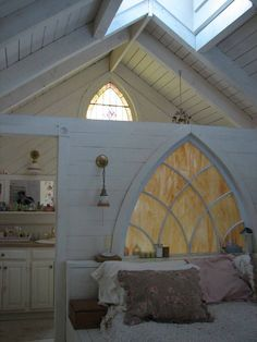 Salvaged cathedral window as a headboard, the bathroom is behind the wall