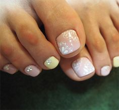 Pedicure done with Muted nude, tan and pastel yellow nails with crystal accents and white free hand lace work toe nail art