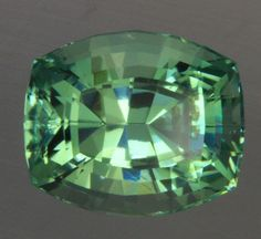 Prasiolite in A Stepped Antique Cushion Cut Weighs 13.43 Carats Cutting quality and fine color give this gem a beauty rarely seen in this blue green quartz from Brazil. In house precision U.S. cutting.