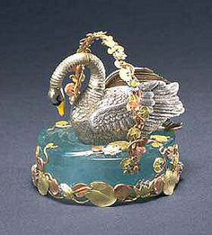 ...Swan Egg Surprise. A miniature swan dressed in platinum, with enameled eyes and beak. The swan rests in a basket dressed with garlands of flowers in three colors of gold, and a large aquamarine. Built into the swan is a mechanism that, when triggered, makes the swan spread its wings and move its feet and tail feathers. Then the head and neck proudly rise up, before settling down again.