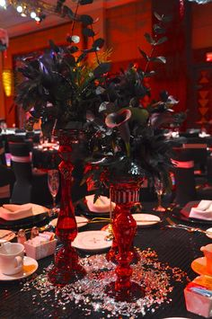 Red candlesticks as floral arrangement. Transparent red glass glows. Contrasting dark flowers. Textured flower arrangements with feathers and calla lilies. Black calla lily arrangement.