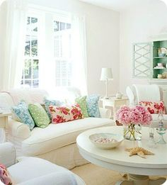 Love the colorful pillows.  If I made slipcovers for my current couch pillows, I wouldn't have to buy or store extra pillows.  Just the slipcovers!  Could do this idea for the seasons and holidays!  I also love the vase of flowers.  Go bright or go home!