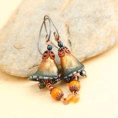 Lucite lilies are hand dyed in shades of mandarin orange that graduates into deep shimmering midnight blue. The earrings are slightly translucent and the veins of the flower can be seen when the sunlight shines through them. Filigree bead caps and copper balls are hand painted in shades of rust and sea and then sealed. [...]