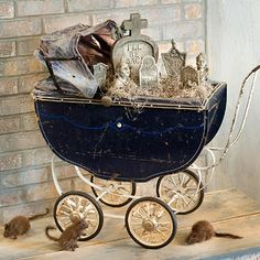 An antique buggy filled with mini tombstones and statues stands as a creepy exhibit. Stuffed rat figures at the wheels round out the Halloween montage. Place on a fireplace hearth or inside your front door.