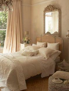 Dormitorio en tonos neutros.  Pared del Cabecero con un espejo.
