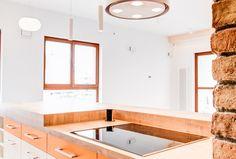 Okap nadwyspowy o walcowatym kształcie w białym kolorze, idealnie wpisuje się w nowoczesne wnętrze kuchni.