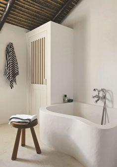 Baignoire ondulante dans l'une des salles de bains. Sur le tabouret de Charlotte Perriand, serviette de toilette Caravane. Drap de bain rayé Hermès.