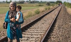Migrants, refugees and asylum seekers: what's the difference?  A woman who has just crossed the border from Serbia into Hungary carries her child along a railway line that links the two countries