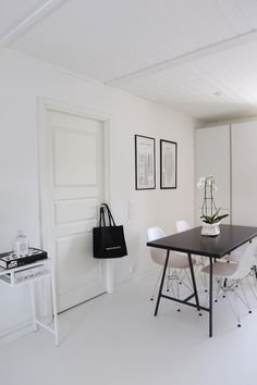 Monochrome Scandinavian dining area with airy, minimalist furniture. The black table really takes center stage.