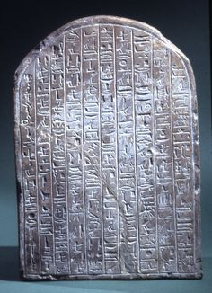 Round-topped limestone stela of Neferabu: inscribed on both sides in shallow sunk relief. The front is divided into two registers; on the upper Ptah, in his usual mummy form, sits on a block throne in a booth adorned with a garland of flower petals. Before Ptah is a table heaped with bread and plant offerings. At the top are four ears, a pair of raised arms, and two eyes, designed to assure the attention of the god and a successful response to the prayer. The lower register displays an image…