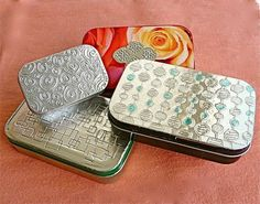 How to Emboss a metal tin, or other surface -- Small candy tins, such as Altoids tins, emptied and cleaned  Aluminum foil tape  Scissors  Plastic spoon  X-Acto knife  Self-healing cutting board
