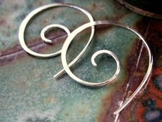 These classy, simple earrings are hand-forged sterling silver swirly hoops. The smooth flat surfaces reflect the light beautifully. Comes with post backs in case you wish to use them.  Measurement: approx. 1 1/4 at the longest point (3cm)  ***These earrings are being created for you when you order and may vary a little from the photos.   Jewelry, Earrings, Hoops, Spiral Sterling Silver Metalwork - Sculpted Artisan, Bespoke