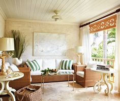 Exquisite outdoor living room uses durable furnishings like a wicker sofa and chair. A white, green and tobacco palette echo the natural landscape beyond the white gauzy curtains