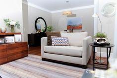 Sala de estar com tapete listrado, sofá claro, mesa de apoio, espelho redondo, flores, móvel em madeira, piso de madeira. Sala decorada, decoração. Repaginada na decoração sala de estar e jantar do apto