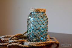 This mason jar has been dyed blue and fish netting has been added along with twine/rope at the top. This jar is perfect decor for your cottage or