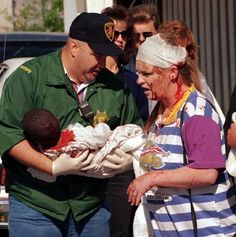 A police officer helps victims of the Oklahoma City bombing on April 19, 1995.