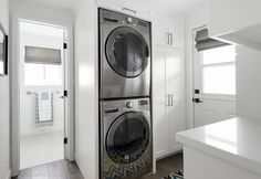 Small white laundry room features floor to ceiling cabinets placed next to a stacked washer and dryer tucked into the wall alongside a blue, yellow, brown and black chevron rug.
