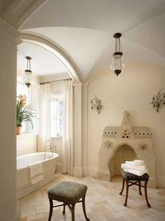 7This wide soaking tub in a tile enclosure rests in the center of the bathroom. A narrow barrel vault is surrounded by crown molding on either side. Dual archways lead into a secondary space behind the tub.