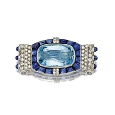 Aquamarine, sapphire and diamond brooch, Cartier, Paris, circa 1930    Centering a cushion-shaped aquamarine weighing approximately 13.90 carats, bordered by buff-top calibré-cut sapphires and pavé-set single-cut and old European-cut diamonds weighing approximately 1.50 carats, the sides accented with sugarloaf cabochon sapphires, mounted in platinum, signed Cartier, Paris,