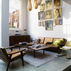 A series of Vladimir Tretchikoff-style 1970s portraits complement the Danish modern furniture. via remodelista