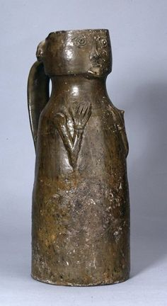 Pottery jug with green glaze depicting human face at front with arms beneath. The arms are formed of applied strips and are bent at the elbow so that the gloved hands are pressed against the body at shoulder level. The hair is represented by a strip of clay above the top of the handle. This is decorated with pierced holes and short, incised lines, probably representing braiding. Restored from fragments.  Medieval 14thC(early) Excavated/Findspot: Worcester Cathedral,  Height: 39.7 centimetres