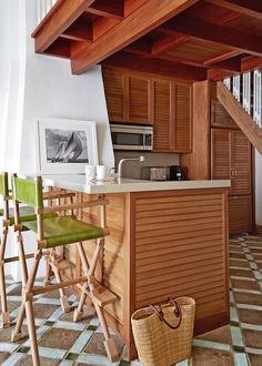 Louvered mahogany millwork is another elegant nod to nautical design in the kitchen, where director's-style stools sport vegetable-dyed goatskin. See more from this Connecticut boathouse now.