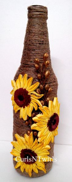 A beer bottle wrapped up in brown jute rope and with quilled sunflowers in yellow around it .: