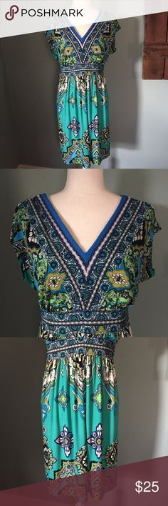 """Kiara Boho Multi-Color V-Neck Dress Size Large This Kiara dress is in excellent condition.  It is size large with the following measurements: Length 36"""", Bust 19"""" flat, Waist 16"""" flat.  It is 95% polyester and 5% spandex. It has a v neck in the front as well as in the back.  It has a teal background with a multi-color print in turquoise, green, navy, white and black. Kiara Dresses"""
