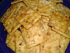 Crack-Tastic Crackers   1 1/2 sticks butter, melted 1 packet ranch dressing mix 2 T. red pepper flakes 1/2 tsp. garlic powder 2 sleeves saltine crackers parmesan cheese  In a large bowl combine melted butter, dressing mix, pepper flakes, and garlic powder.  Add crackers, 1 sleeve at a time, and gently with your hand toss to coat the crackers.  Let sit in the bowl while the oven preheats to 250 degrees.  Line a large cookie sheet with tin foil.  Spread crackers out on tin foil and bake for 15…