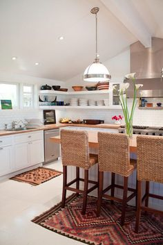 nice  #kitchen whit a semi-bar table, using for decorate it a pairs of carpets... good idea!