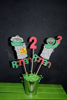 Oscar The Grouch Centerpiece Stick With Childs Name And Age    I make them out of cardstock Paper then I put them on a wood stick.    I can make