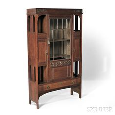 Gerson & Wolf Arts & Crafts Display Cabinet  Oak, glass, brass  Stuttgart, Germany, early 20th century  Rectangular form centered by a beveled glass door with stylized flowers over long drawer, the sides with four open cabinets for display and two cabinets with doors, brass hardware.