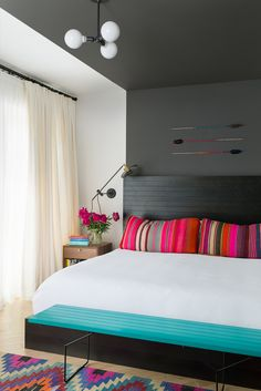 Love the colors!            Master bedroom painted in two tones, a fresh white and a deep grey that lines up with the headboard, wraps up over the ceiling and down the opposite wall.