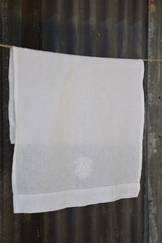 A beautiful, monogrammed linen cloth for wiping the condensation and wine drops when pouring wine or bubbly. Manufactured in India Made from white linen,