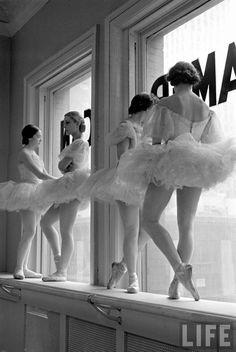 Ballerinas standing on window sill in rehearsal...