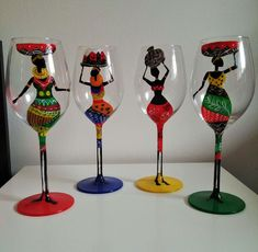 Four wine glasses each with a different lady and different colour of bottom. Hand painted wine glasses with african theme