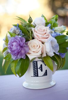 Purple and white flower centerpieces in monogrammed mugs