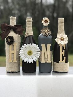 Recycled wine bottles crafted with paint, twine, and letters to spell HOME. These particular bottles are painted in an espresso brown and granite gray. I can customize the colors to fit your needs. Just send me a message with your color preferences.