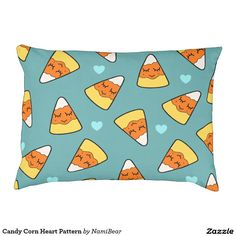 Candy Corn Heart Pattern Dog Bed by NamiBear on Zazzle.com. This is a drawing of a candy corn with a smile on her face with hearts around her. It has a green background.