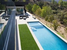 Infinity Pool Overlooking Forest Scenery* An infinity pool overlooks a hillside that falls away steeply from a striking contemporary patio. Water is used architecturally in Modernist design, often as a reflective surface. Here, a tranquil pool reflects a unified environment.