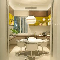 Great office layout in small space: cabinets high, desk around wall, round table.