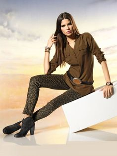 Leopard printed trousers with a long shirt and a pair of black ankle boots.
