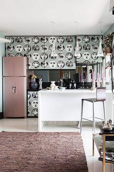 Moderna e feminina ao mesmo tempo, a cozinha conjuga com a sala de estar do apartamento. A estrela do ambiente é a geladeira rosa