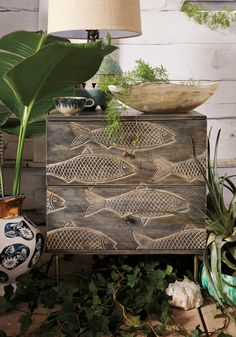 The Handcarved Streamlet Nightstand is brass-legged with fish handcarved in mango wood.